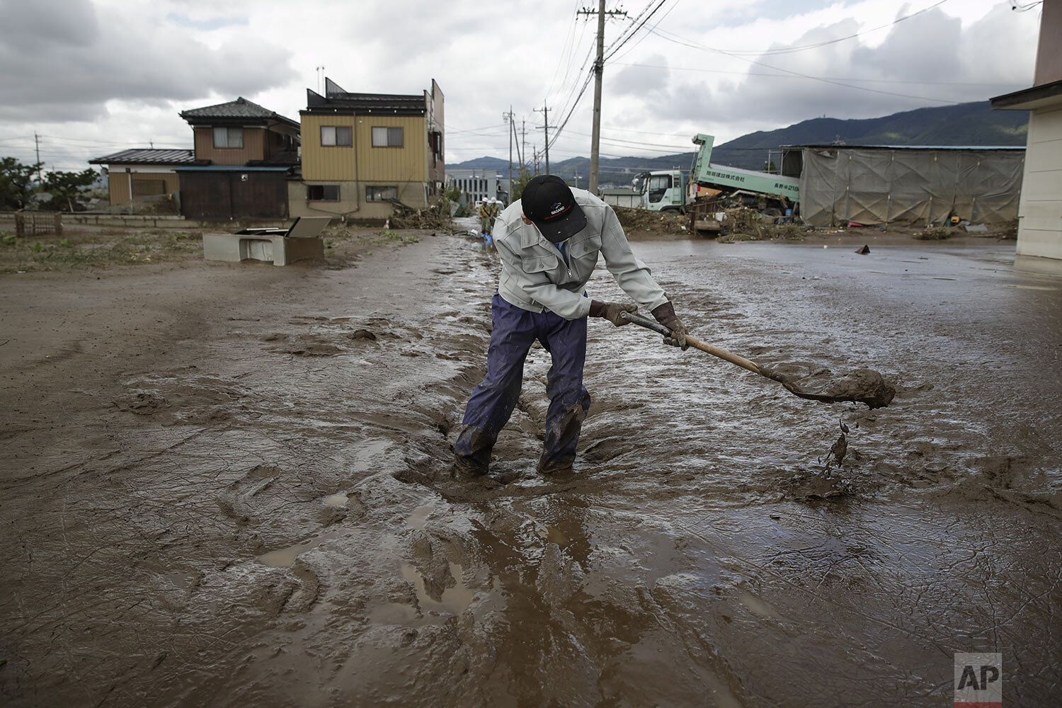 A man uses a shovel to scoop mud in a neighborhood devastated by Typhoon Hagibis Tuesday, Oct. 15, 2019, in Nagano, Japan.  (AP Photo/Jae C. Hong)