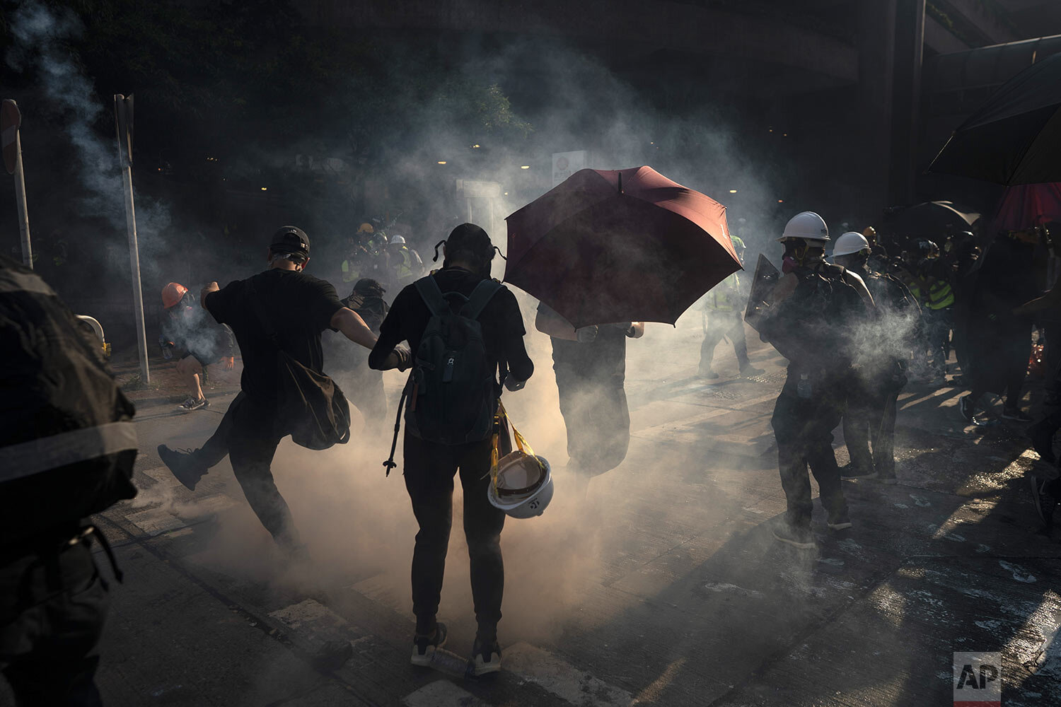 A protestor kicks back an exploded tear gas shell in Hong Kong, Tuesday, Oct. 1, 2019. Hong Kong police shot a protester at close range, leaving him bleeding from his shoulder and howling on the ground, in a fearsome escalation of anti-government demonstrations that spread across the semi-autonomous Chinese territory on Tuesday.  (AP Photo/Felipe Dana)