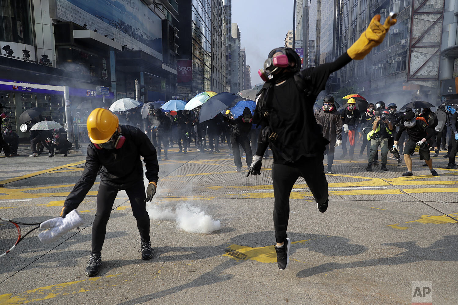 Protesters throw tear gas canisters fired by riot policemen during a rally in Hong Kong, Sunday, Oct. 20, 2019.  (AP Photo/Mark Schiefelbein)