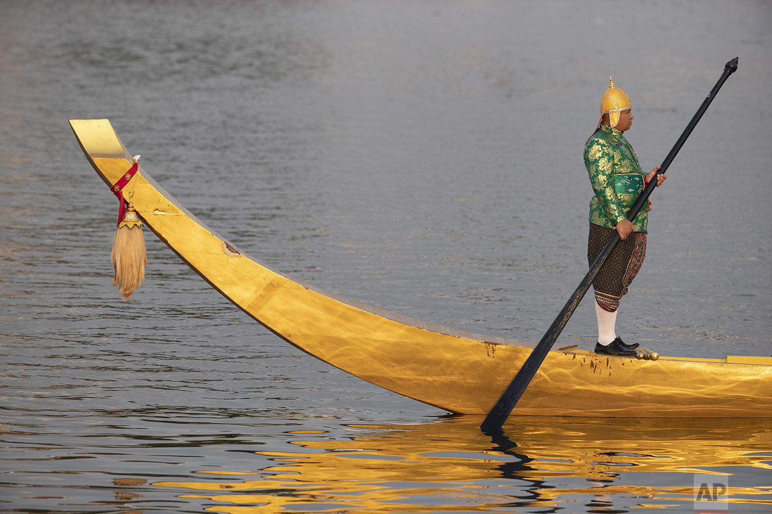 A lone oarsman stands on his boat during the dress rehearsal for the Royal barge ceremony on the Chao Phraya river Bangkok, Thailand, Monday, Oct. 21, 2019. (AP Photo/Sakchai Lalit)