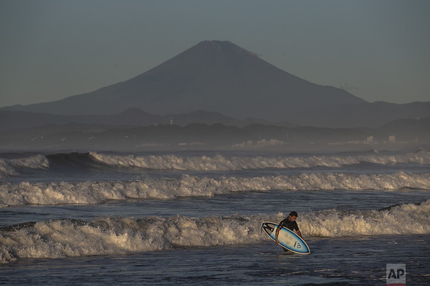 A surfer walks out of the water as Mount Fuji is visible in the distance after Typhoon Hagibis passed through the area, Sunday, Oct. 13, 2019, in Fujisawa, west of Tokyo. (AP Photo/Jae C. Hong)