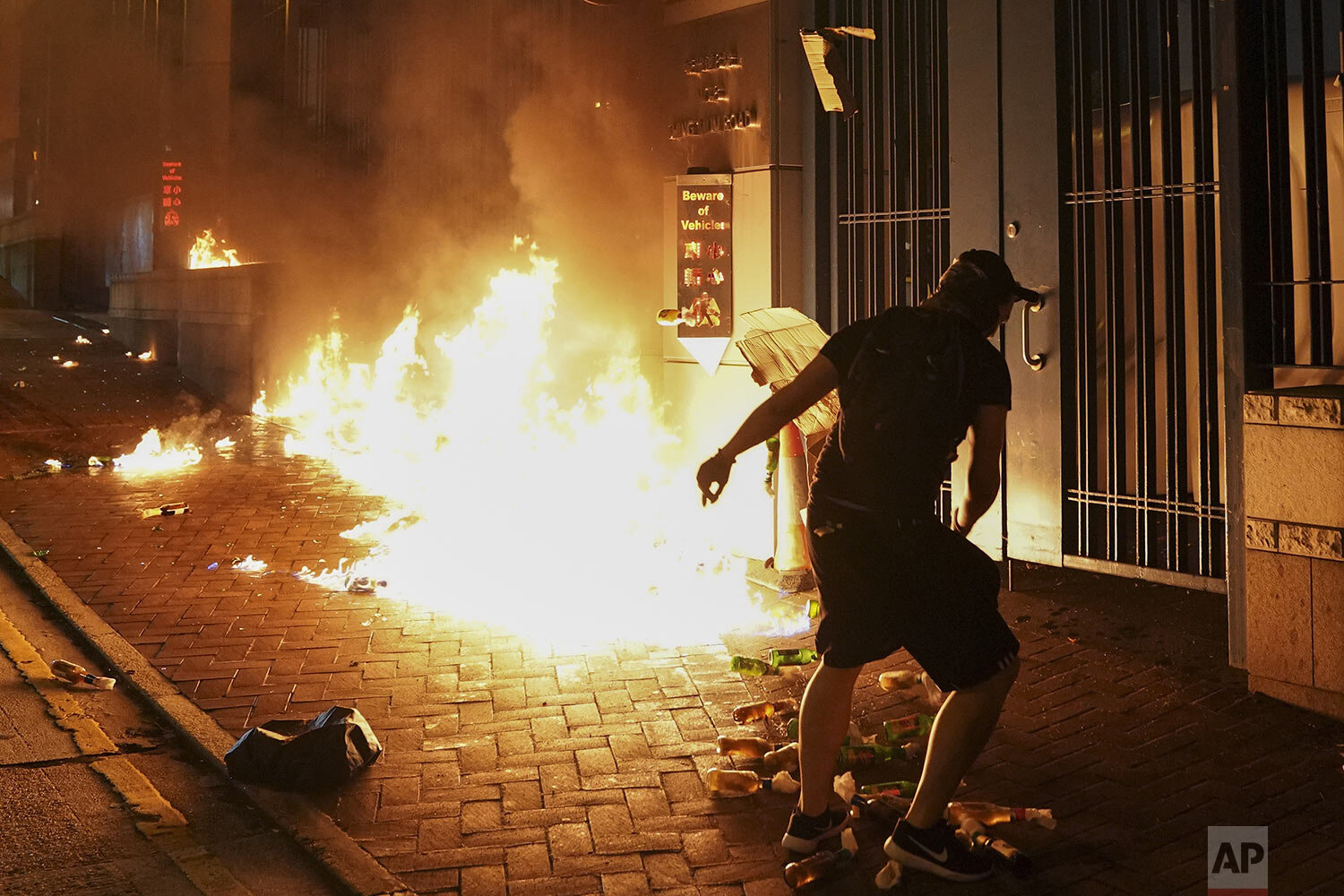 Protesters throw petrol bomb outside the Tsuen Wan police station in Hong Kong, Wednesday, Oct. 2, 2019.  (AP Photo/Vincent Thian)