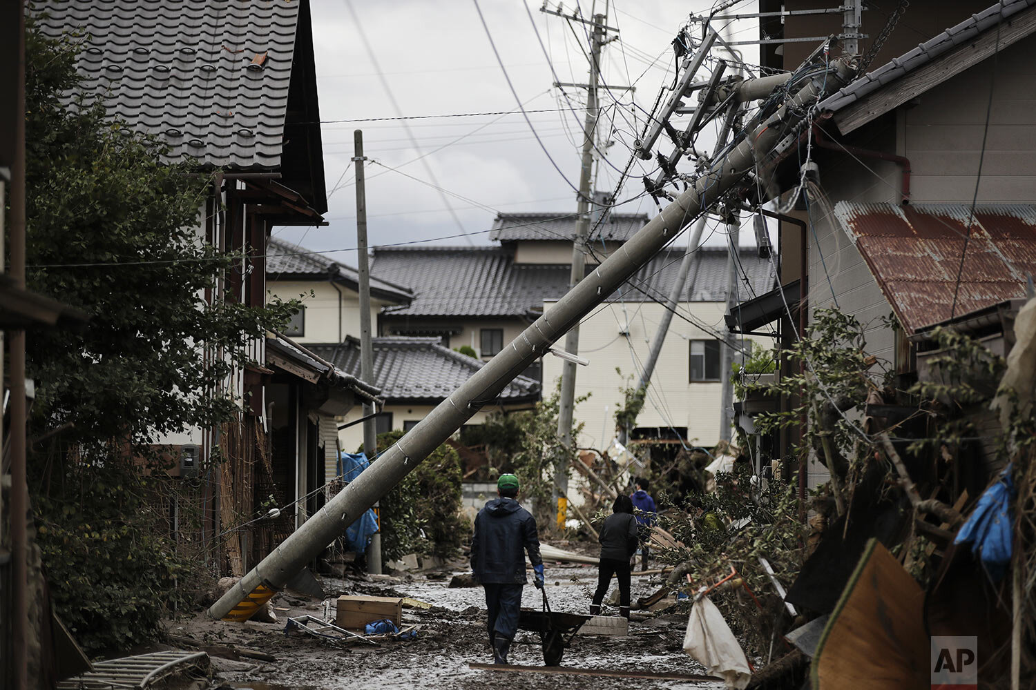 Residents walk along the mud-covered road in a neighborhood devastated by Typhoon Hagibis, in Nagano, Japan, Tuesday, Oct. 15, 2019. (AP Photo/Jae C. Hong)