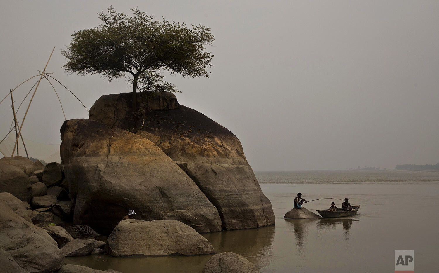 A fisherman sits on a rock to catch fish in the river Brahmaputra in Kasoshila village on the outskirts of Gauhati, India, Monday, Oct. 21, 2019. (AP Photo/Anupam Nath)