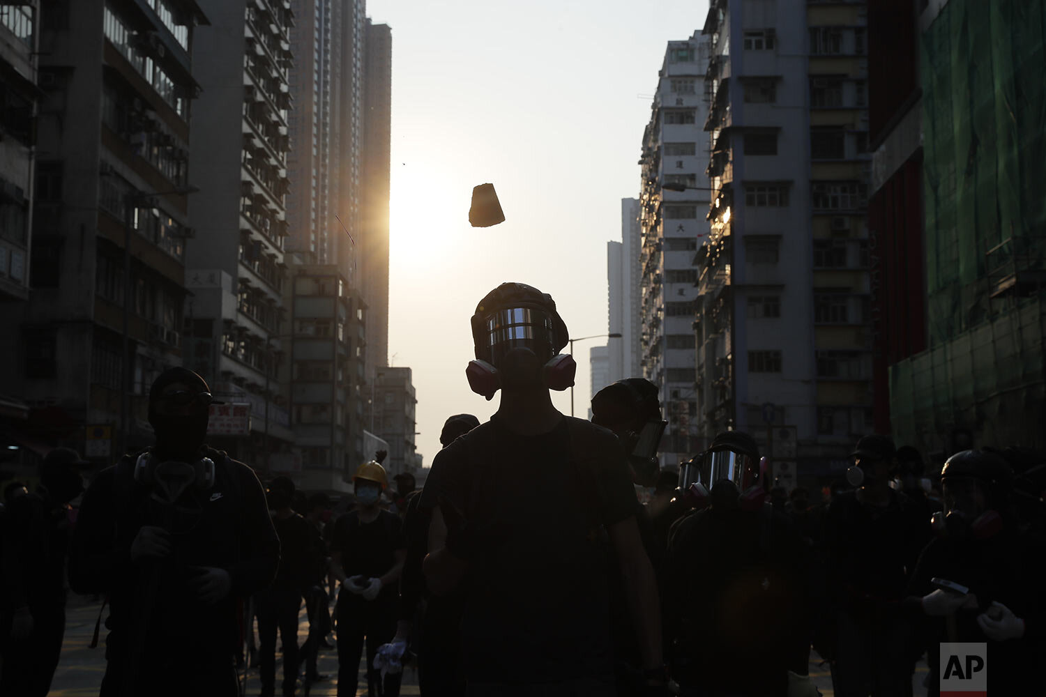 Protestors wearing masks watch as they clash with police in Hong Kong, Sunday, Oct. 20, 2019. (AP Photo/Kin Cheung)