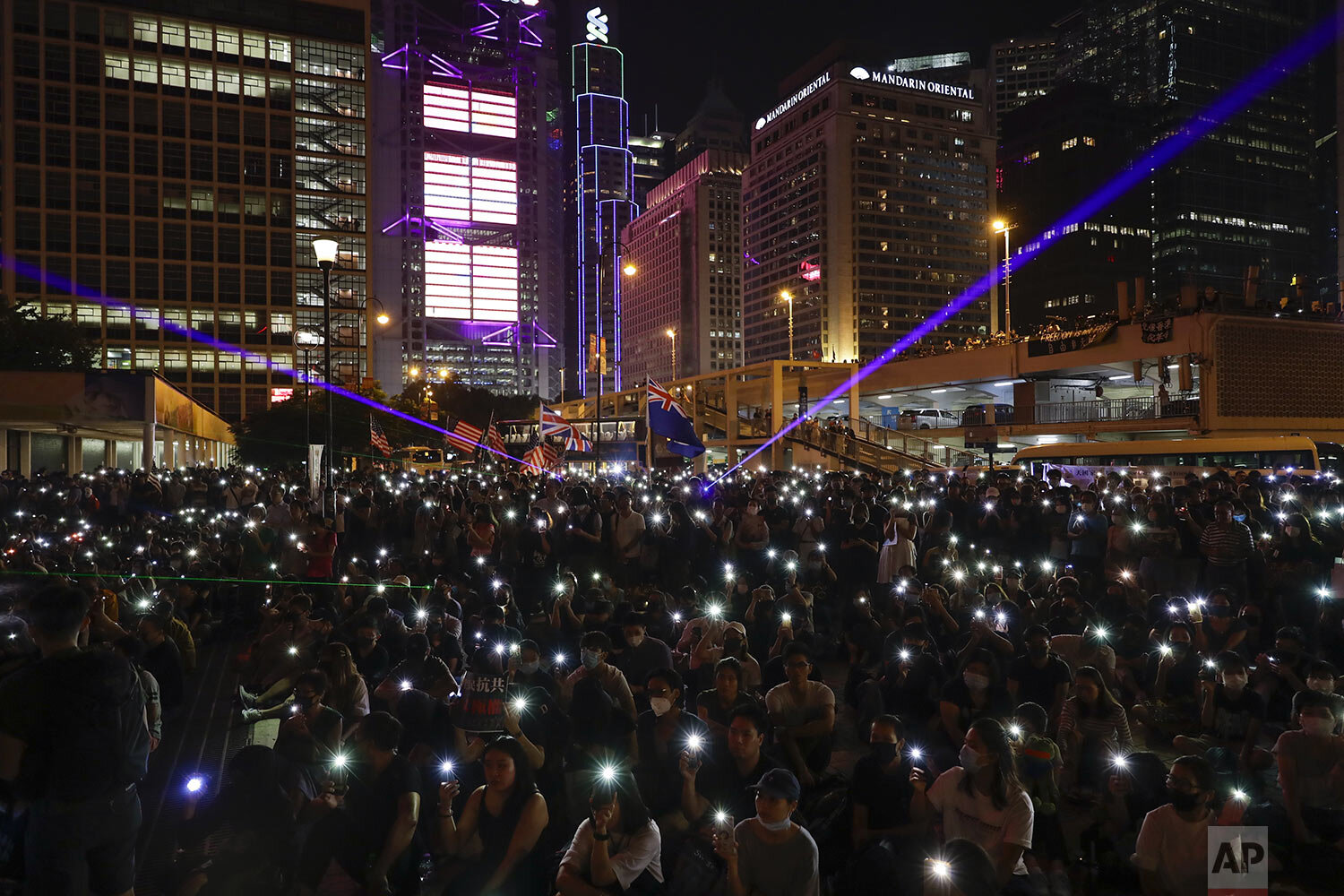 Protesters flash their smartphone lights during a rally at Edinburgh Place in Hong Kong, Saturday, Oct. 19, 2019. (AP Photo/Mark Schiefelbein)