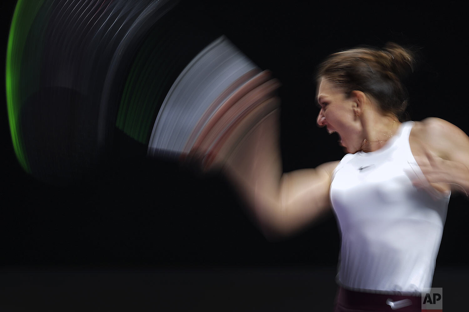 Simona Halep, of Romania, hits a return shot against Bianca Andreescu of Canada during their WTA Finals tennis tournament in Shenzhen, China's Guangdong province, Monday, Oct. 28, 2019. (AP Photo/Andy Wong)