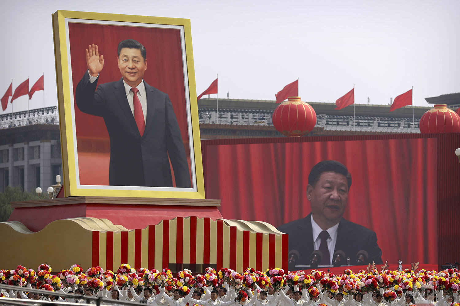 Participants cheer beneath a large portrait of Chinese President Xi Jinping during a parade to commemorate the 70th anniversary of the founding of Communist China in Beijing, Tuesday, Oct. 1, 2019. (AP Photo/Mark Schiefelbein)