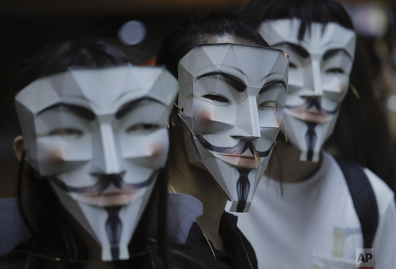 Protesters wear masks in Hong Kong, Friday, Oct. 18, 2019. Hong Kong pro-democracy protesters are donning cartoon/superheroes masks as they formed a human chain across the semiautonomous Chinese city, in defiance of a government ban on face coverings. (AP Photo/Kin Cheung)