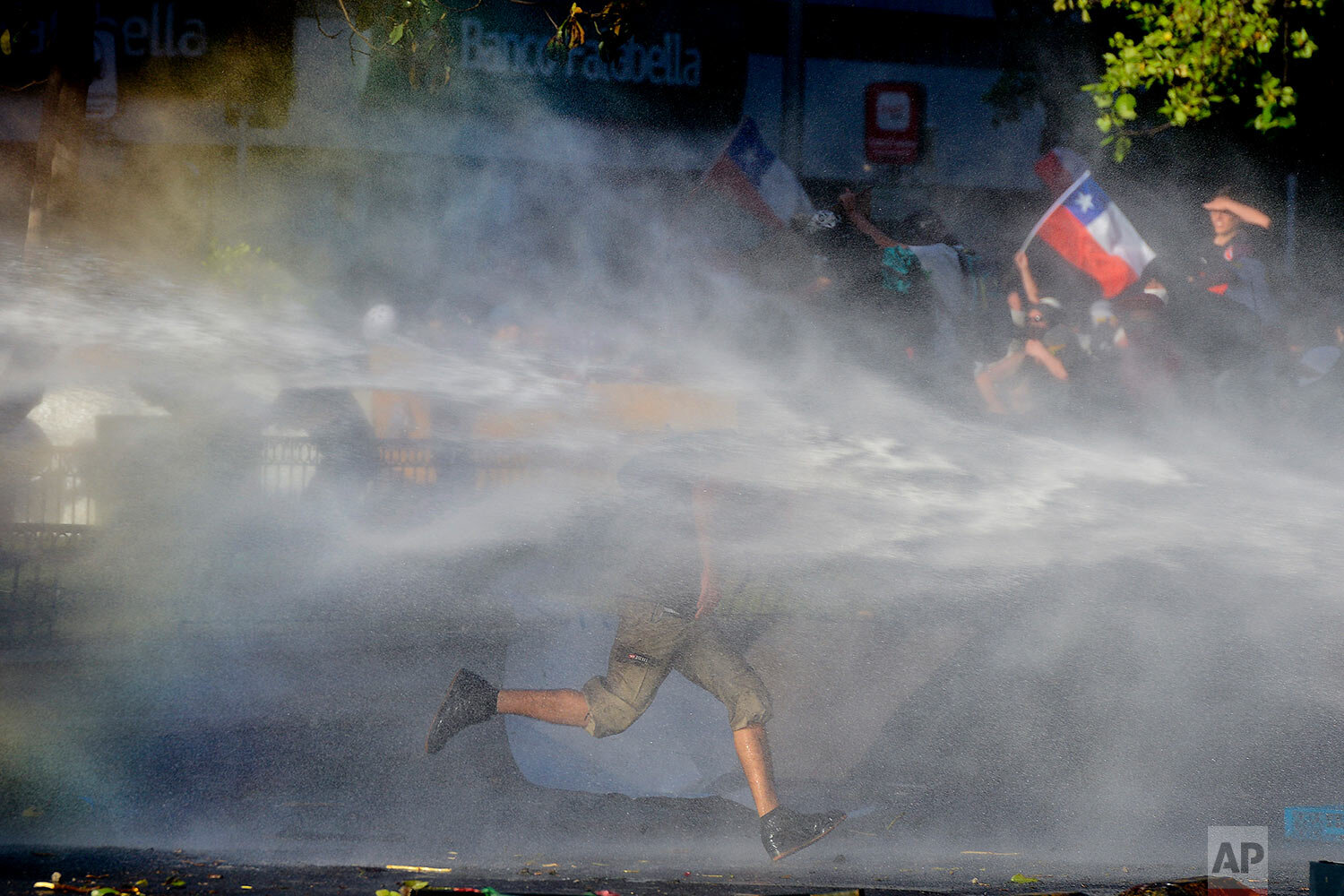 An anti-government protester runs through the spray from a police water cannon in Santiago, Chile, Monday, Oct. 28, 2019. Fresh protests and attacks on businesses erupted in Chile Monday despite President Sebastián Piñera's replacement of eight important Cabinet ministers with more centrist figures, and his attempts to assure the country that he had heard calls for greater equality and improved social services. (AP Photo/Matias Delacroix)