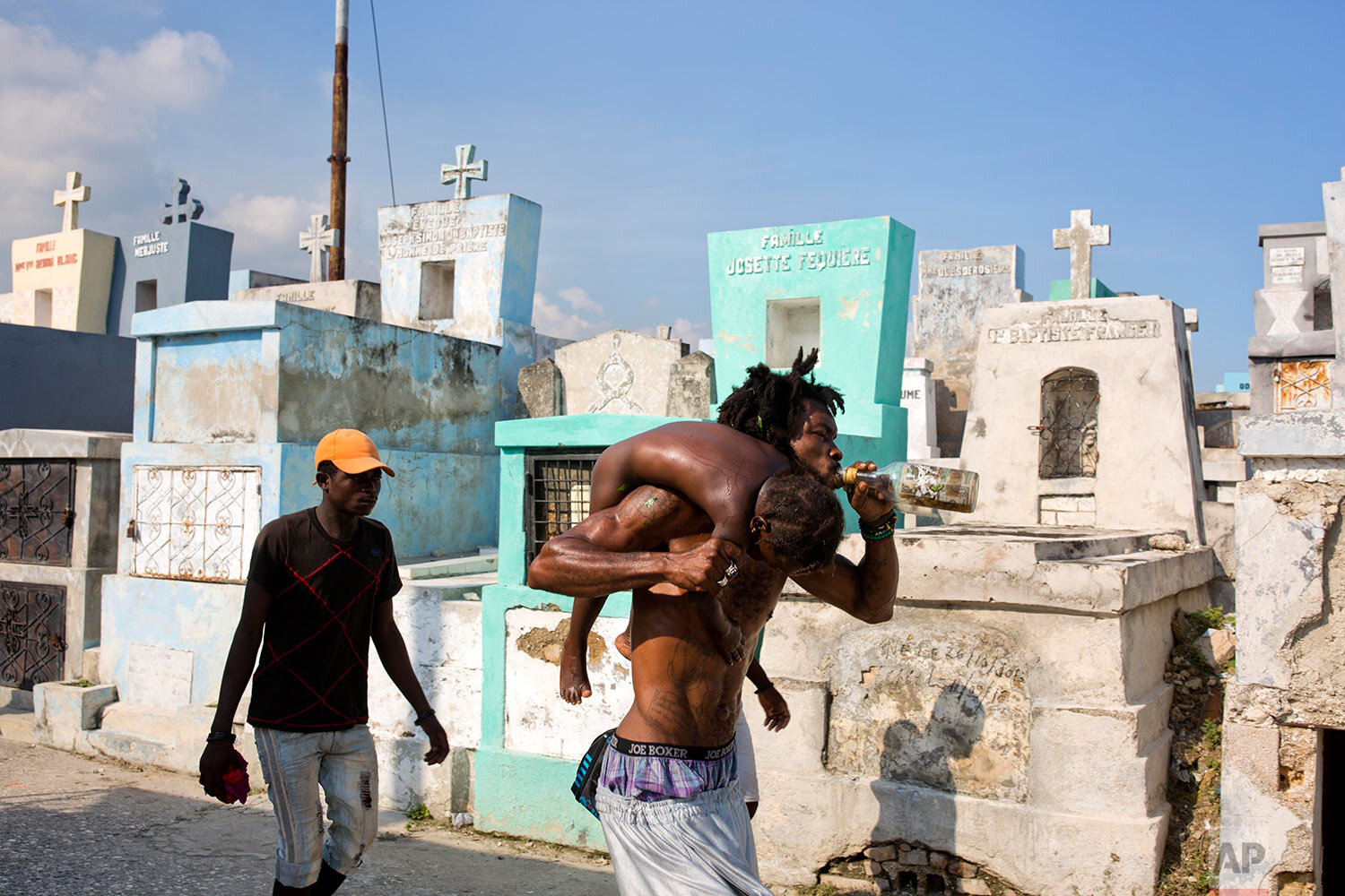 A voodoo priest claiming to be possessed with a Gede spirit carries a sick girl for treatment during the annual Voodoo festival of Fete Gede in Port-au-Prince, Haiti, Friday, Nov. 1, 2019. (AP Photo/Dieu Nalio Chery)