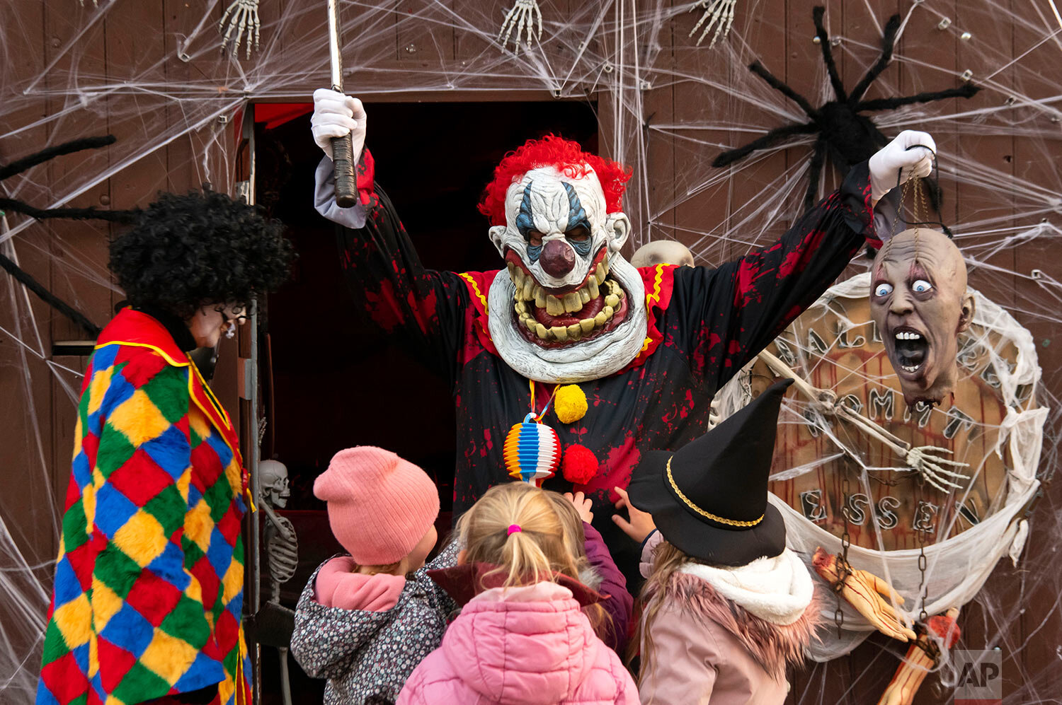 Mario Leicht, center, and his wife, wear costumes as horror clowns at their house decorated for Halloween in Walschleben near Erfurt, Germany, Thursday, Oct. 31, 2019. The whole house facade and the front garden are decorated with dolls, spiders, skulls and inside with mini-ghosts, vampires, skeletons, zombies and almost 50 spiders. He decorates the house for Halloween every year since 2011. (AP Photo/Jens Meyer)