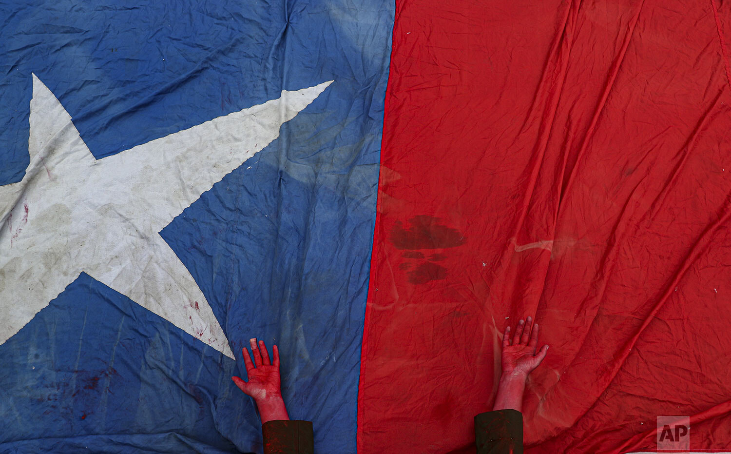 A performer places her hands, covered in red paint to symbolize blood, on a Chilean flag to honor protesters who have died amid days of demonstrations calling for better pay, pensions, schools, housing and medical care, among many other demands, during an anti-government music concert in Santiago, Chile, Sunday, Oct. 27, 2019. While most protests have been peaceful, some have devolved into riots and looting, and the government says at least 20 people have died. (AP Photo/Esteban Felix)