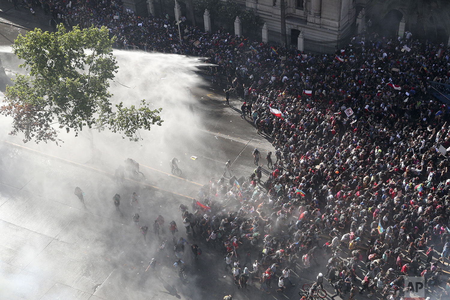 Police sprays water on anti-government demonstrators in Santiago, Chile, Monday, Oct. 28, 2019. President Sebastian Pinera announced changes in his cabinet in hopes of bringing peace back to the streets after days of protests that originally started over a hike in subway fares and have grown into a wider range of demands. (AP Photo/Esteban Felix)