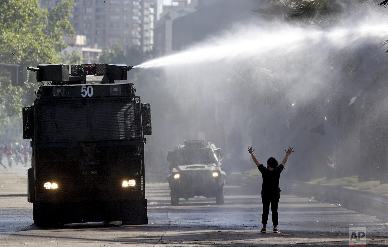 """A protester holds her hands up toward a police truck spraying a water canon at students and union members marching in Santiago, Chile, Monday, Oct. 21, 2019. Protesters defied an emergency decree and confronted police in Chile's capital on Monday, continuing disturbances that have left fatalities and led the president to say the country is """"at war."""" (AP Photo/Miguel Arenas)"""