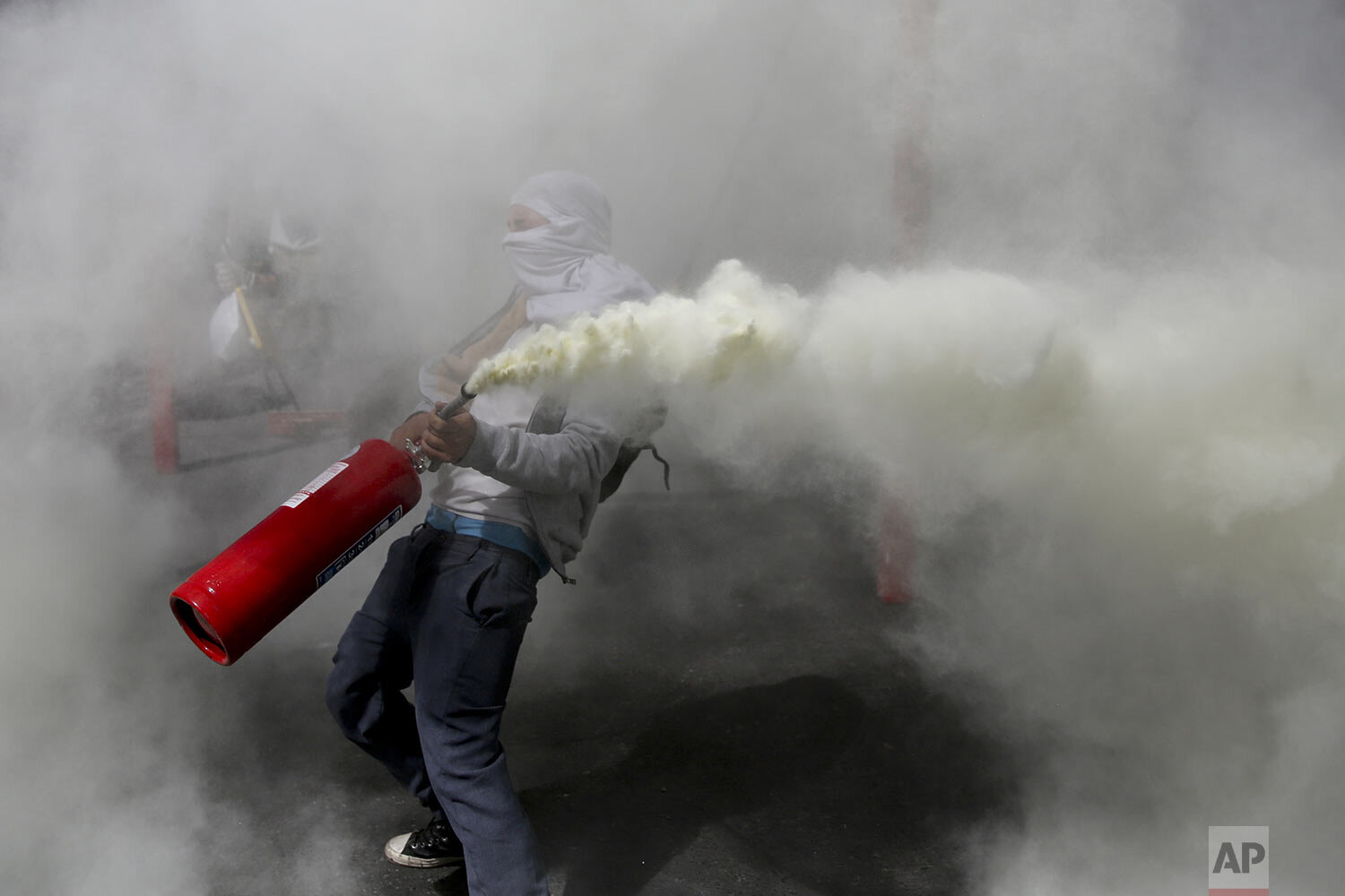 An anti-government demonstrator sprays a fire extinguisher during clashes with police in Santiago, Chile, Monday, Oct. 28, 2019. (AP Photo/Rodrigo Abd)