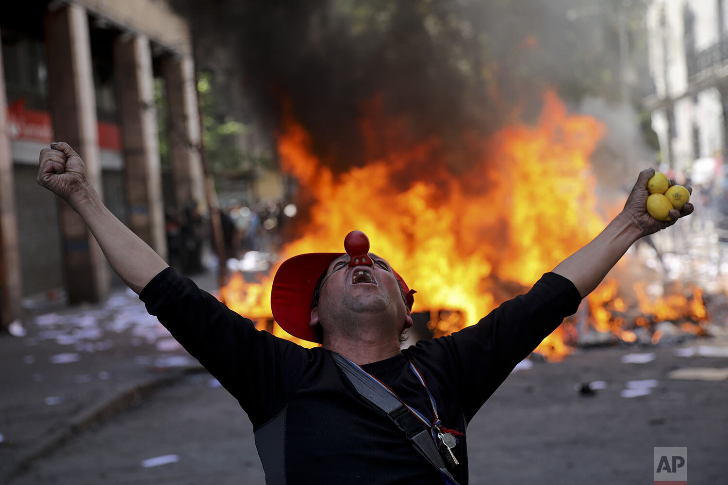 An anti-government demonstrator screams in font of a burning barricade in Santiago, Chile, Tuesday, Oct. 22, 2019. (AP Photo/Rodrigo Abd)