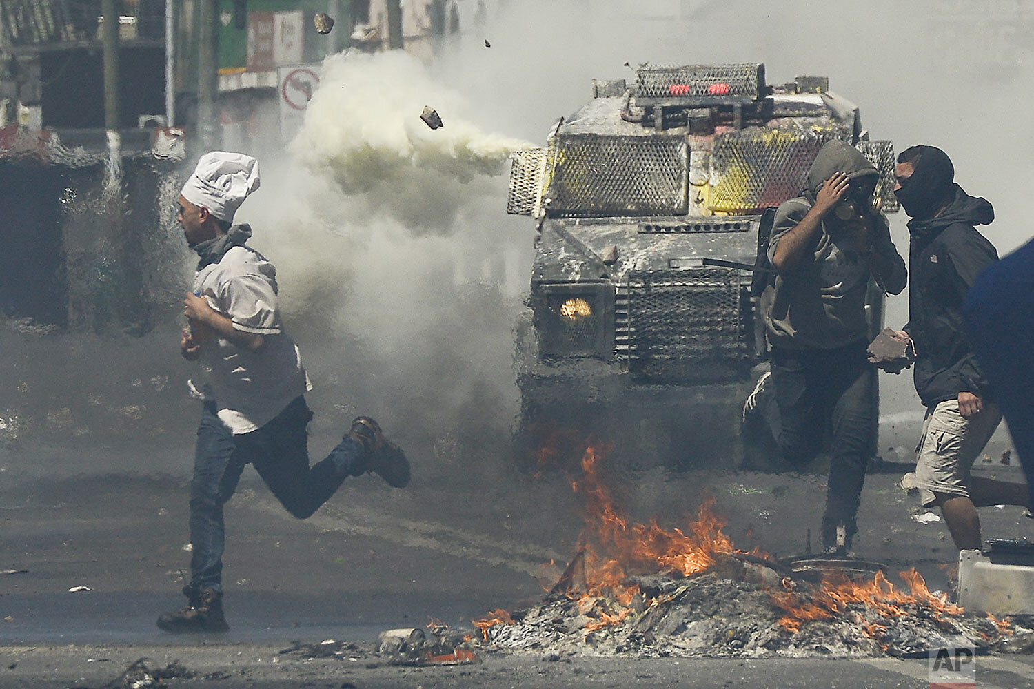 A man wearing a chef's hat runs for cover as anti-government protesters clash with police in Valparaiso, Chile, Thursday, Oct. 24, 2019. (AP Photo/Matias Delacroix)