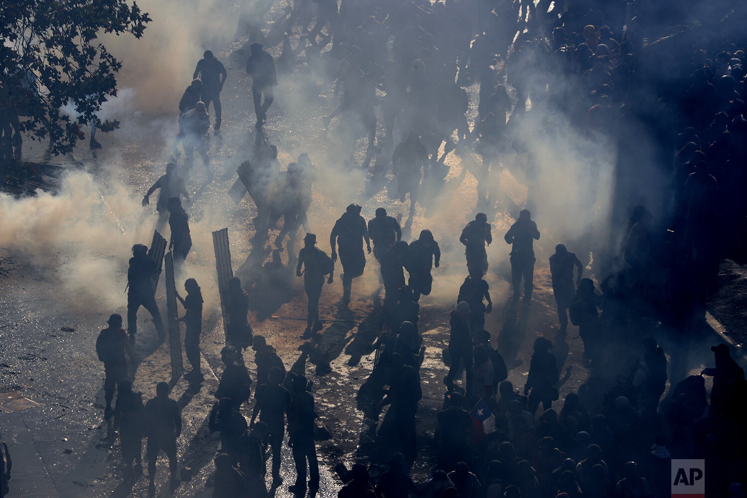 Protesters move amid tear gas launched by police during ongoing demonstrations triggered by an increase in subway fares in Santiago, Chile, Monday, Oct. 21, 2019. (AP Photo/Esteban Felix)