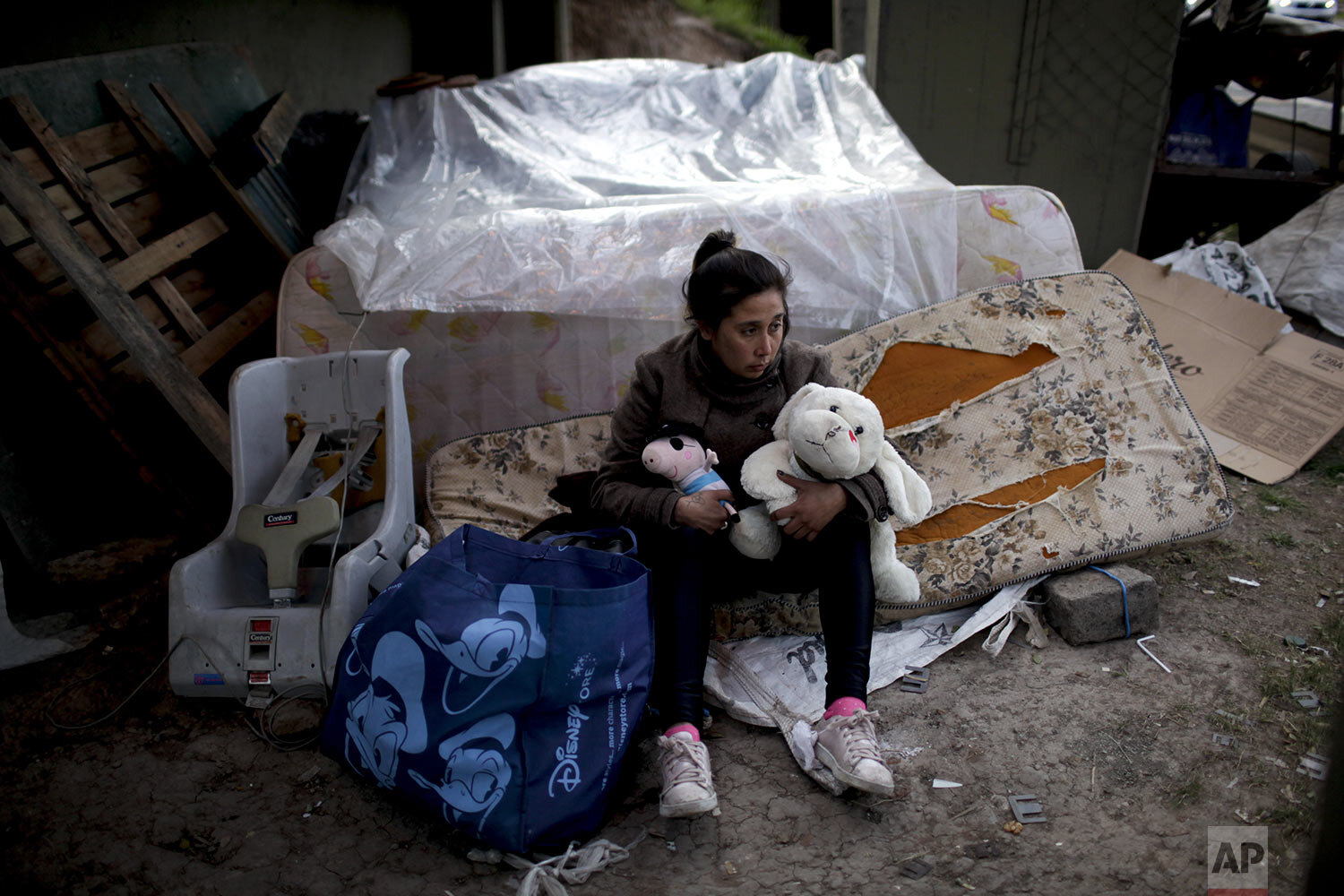"""In this Sept. 19, 2019 photo, Macarena Contreras holds stuffed animals she plucked from the garbage for her three children as she poses for a photo where she lives homeless under a bridge in Buenos Aires, Argentina. Contreras, 31, lost her job as a nanny two years ago, and her children, ages 3 to 8, live with her mother. The single mother said she hasn't been able to find a job as a nanny because people are cutting back their expenses, and that she started sleeping under a bridge after she and her partner broke up. """"We're in a war where Argentines are fighting against Argentines,"""" she says, feeling there is a lack of solidarity with people like her and paranoia that the poor are thieves. """"The street is not a life for anyone."""" (AP Photo/Natacha Pisarenko)"""
