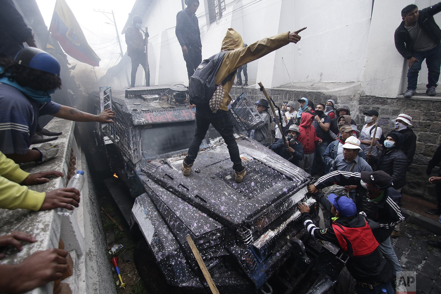 Anti-government demonstrators commandeer an armored vehicle during a nationwide strike against President Lenin Moreno and his economic policies , in Quito, Ecuador, Wednesday, Oct. 9, 2019. Ecuador's military has warned people who plan to participate in a national strike over fuel price hikes to avoid acts of violence. The military says it will enforce the law during the planned strike Wednesday, following days of unrest that led Moreno to move government operations from Quito to the port of Guayaquil. (AP Photo/Carlos Noriega)