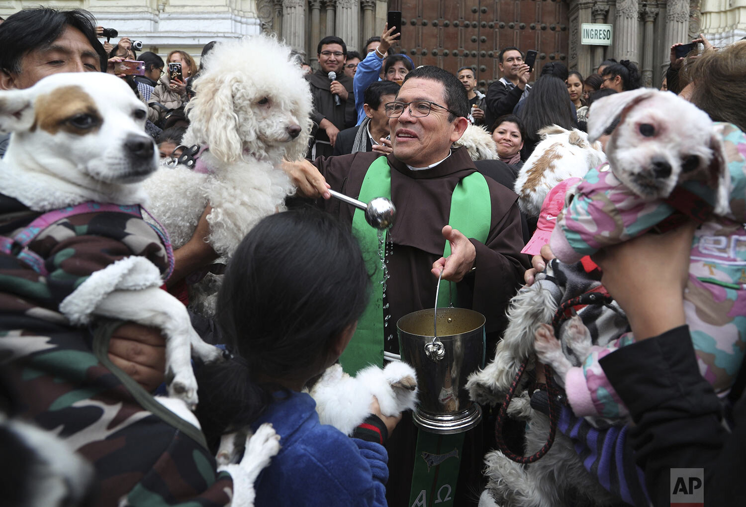 Catholic Priest Fermin Pena blesses animals with holy water outside San Francisco church in Lima, Peru, Sunday, Oct. 6, 2019. The annual event is held in honor of Saint Francis, the patron saint of ecologists whose feast day is Oct. 4 and who is known for his love of animals. (AP Photo/Martin Mejia)