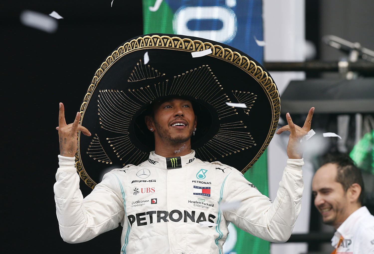 Mercedes driver Lewis Hamilton, of Britain, dons a Mexican Charro hat as he celebrates his victory in the Formula One Mexico Grand Prix auto race at the Hermanos Rodriguez racetrack in Mexico City, Sunday, Oct. 27, 2019. (AP Photo/Rebecca Blackwell)