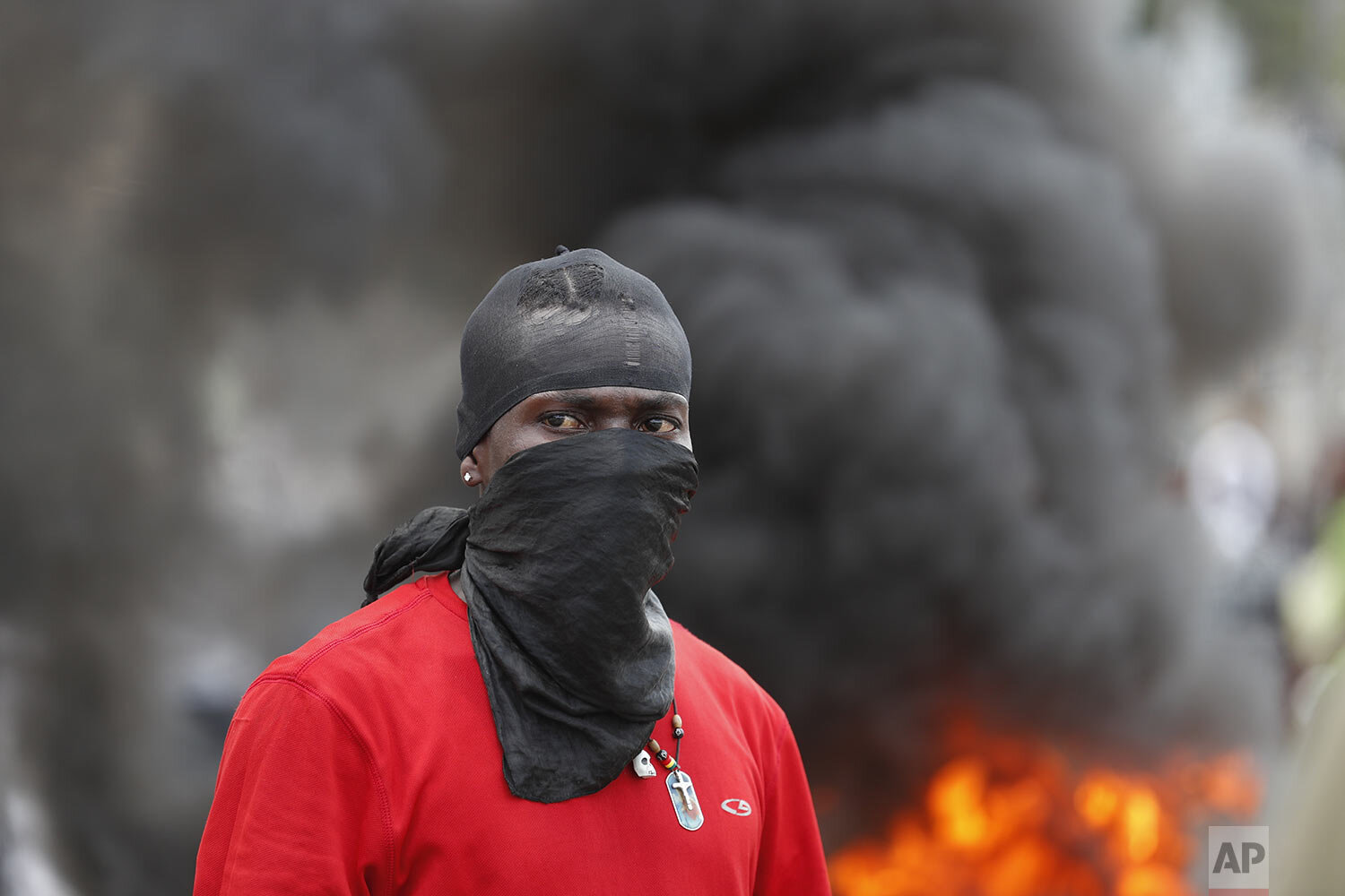 A demonstrator stands in front of a burning barricade during a protest calling for the resignation of President Jovenel Moise, in Port-au-Prince, Haiti, Friday, Oct. 4, 2019. After a two-day respite from the recent protests that have wracked Haiti's capital, opposition leaders urged citizens angry over corruption, gas shortages, and inflation to join them for a massive protest march to the local headquarters of the United Nations. (AP Photo/Rebecca Blackwell)
