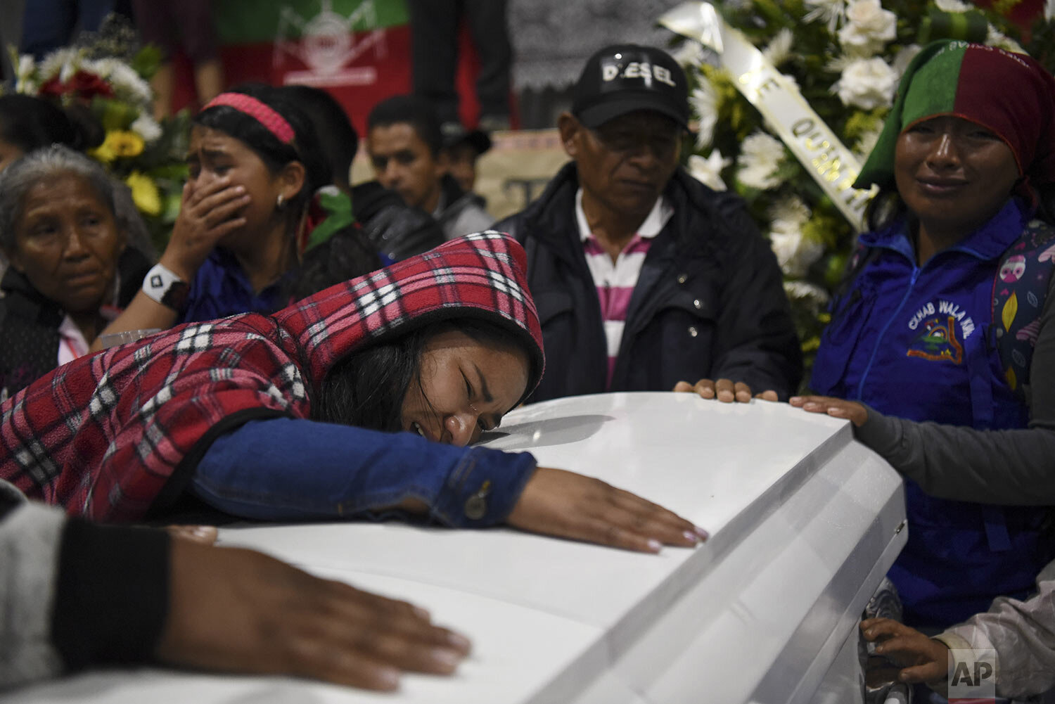 Relatives mourn on the coffin of a slain indigenous leader in Tacueyo, southwest Colombia, Thursday, Oct. 31, 2019. Five people from the Tacueyo reservation were killed late Tuesday when their caravan of armored SUVs was ambushed by gunmen the government says belong to a faction of Revolutionary Armed Forces of Colombia that refused to accept the rebel's group treaty with the government. (AP Photo/Christian EscobarMora)