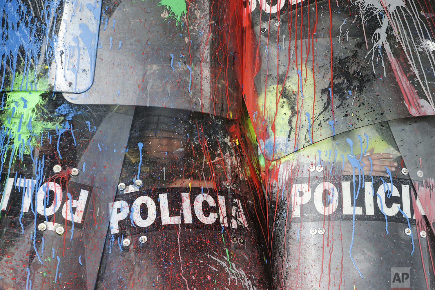 The shields of National Police are covered in paint thrown by protesting students in Bogota, Colombia, Thursday, Oct. 10, 2019. Students are demanding more government resources for education and higher quality universities. (AP Photo/Ivan Valencia)