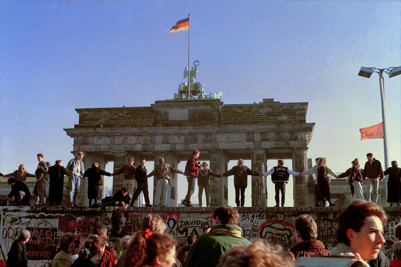Berliners sing and dance on top of the Berlin Wall to celebrate the opening of East-West German borders, Nov. 10, 1989, Berlin. (AP Photo/Thomas Kienzle)