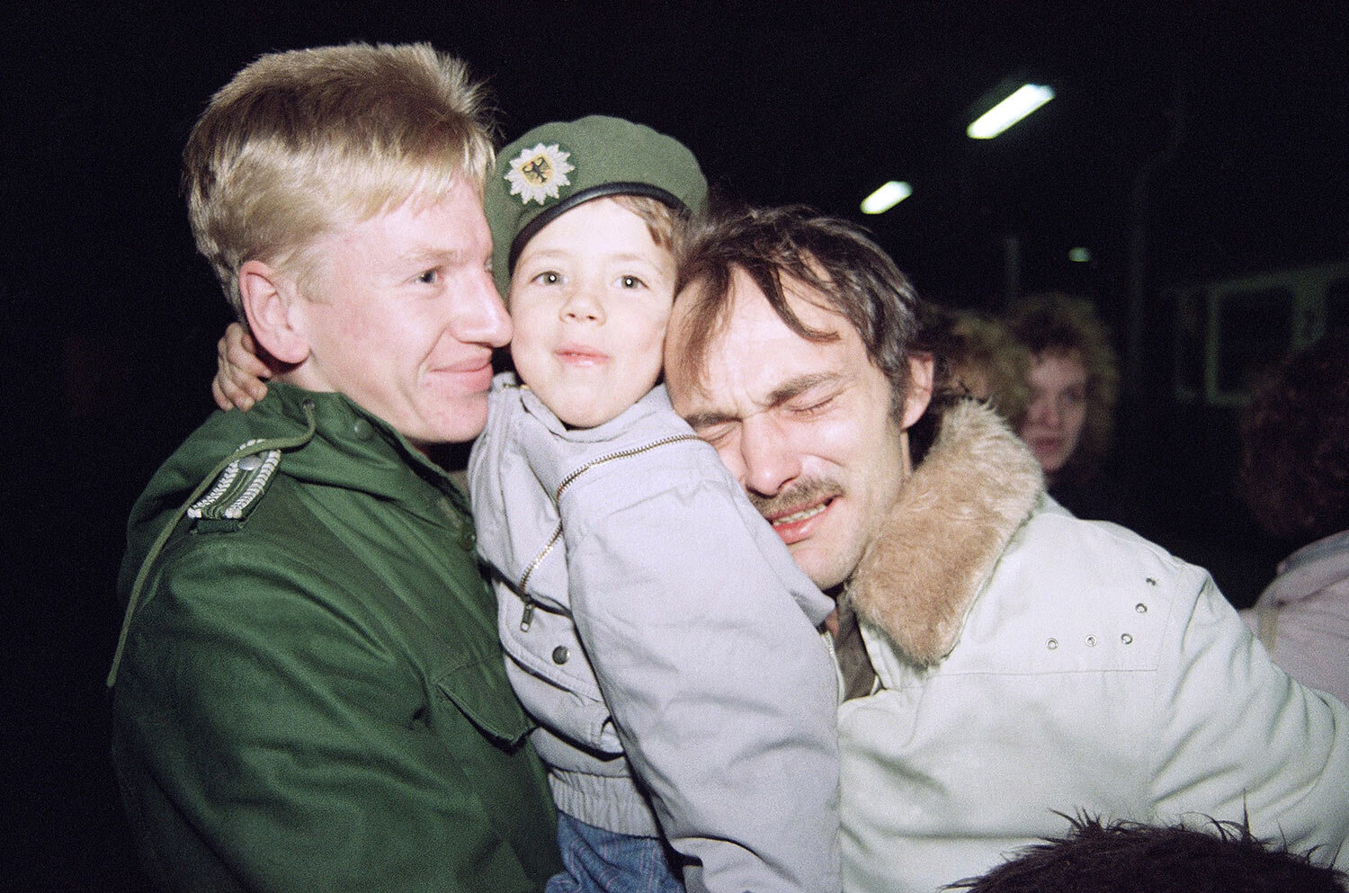 """Heinz Joachim Nickel, right, a member of the East German opposition group """"New Forum,"""" is overcome with emotion as he and his son, Christian, center, arrive in Helmstedt, West Germany by train from East Germany, Nov. 11, 1989. Christian wears a cap belonging to an unidentified West German border guard, left. Nickel said he and his son will return to East Germany. (AP Photo/Claus Eckert)"""