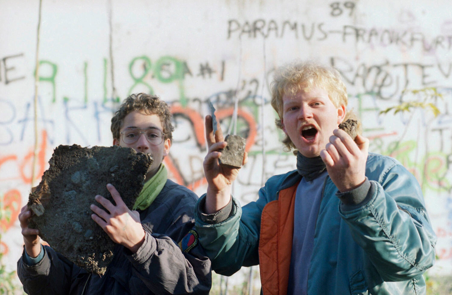Berlin schoolboys proudly show off bricks of the Berlin Wall they found near Brandenburg Gate in Berlin from last night's celebrations at the opening of the East German border to the West, Nov. 10, 1989. (AP Photo/Udo Weitz)