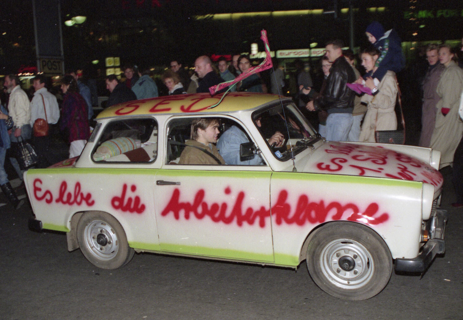 """A Trabant car, made in East Germany, with a graffiti quote, """"Shall the laboring classes live on"""" is pictured driving in West Berlin, West Germany, November 11, 1989, two days after the boarder between the two Germanys was abolished. (AP Photo)"""