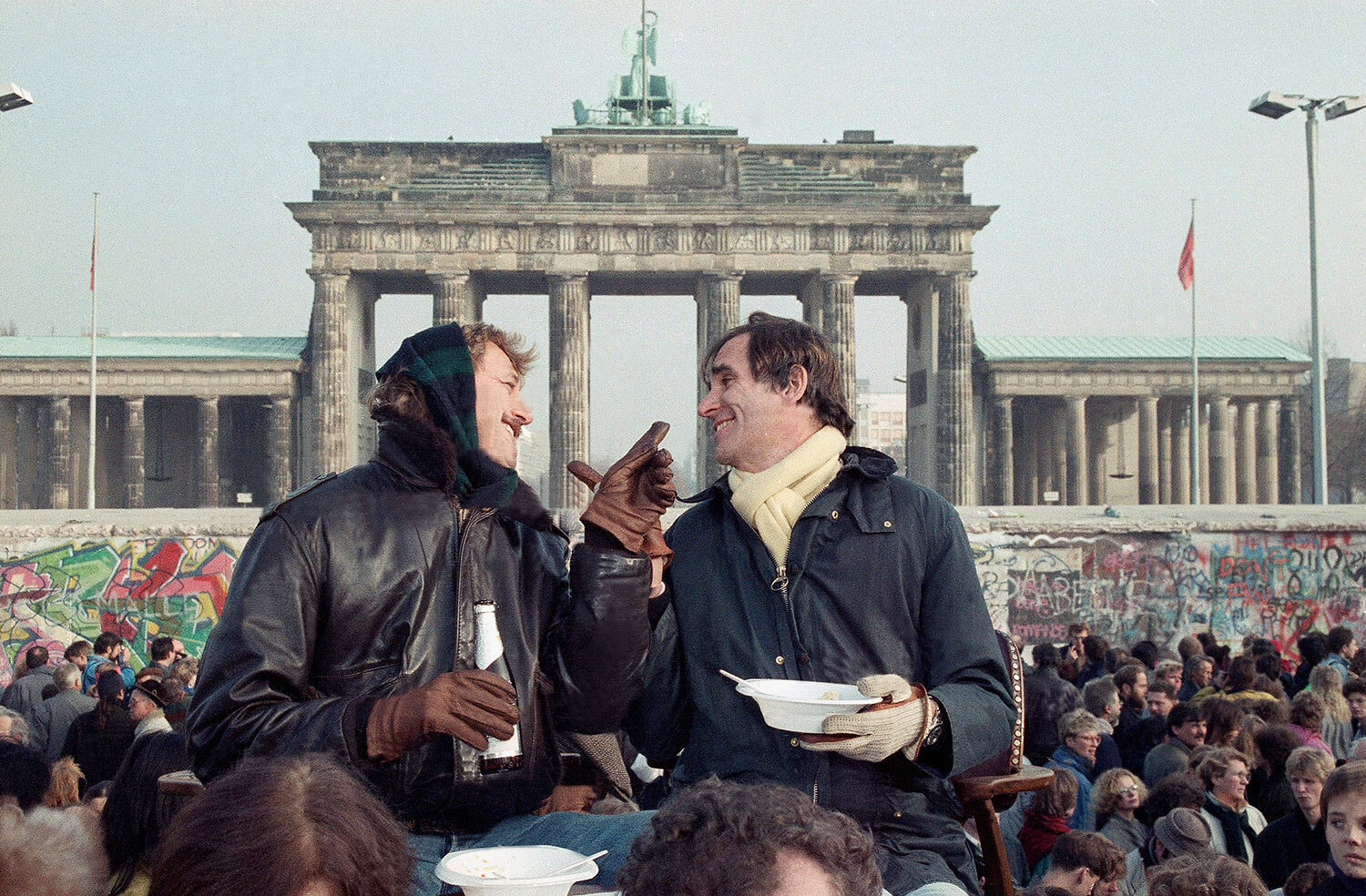 Two Berliners chat in front of Brandenburg Gate in Berlin, Nov. 12, 1989 while having lunch on a visitor's platform near the Berlin Wall. (AP Photo/Lionel Cironneau)