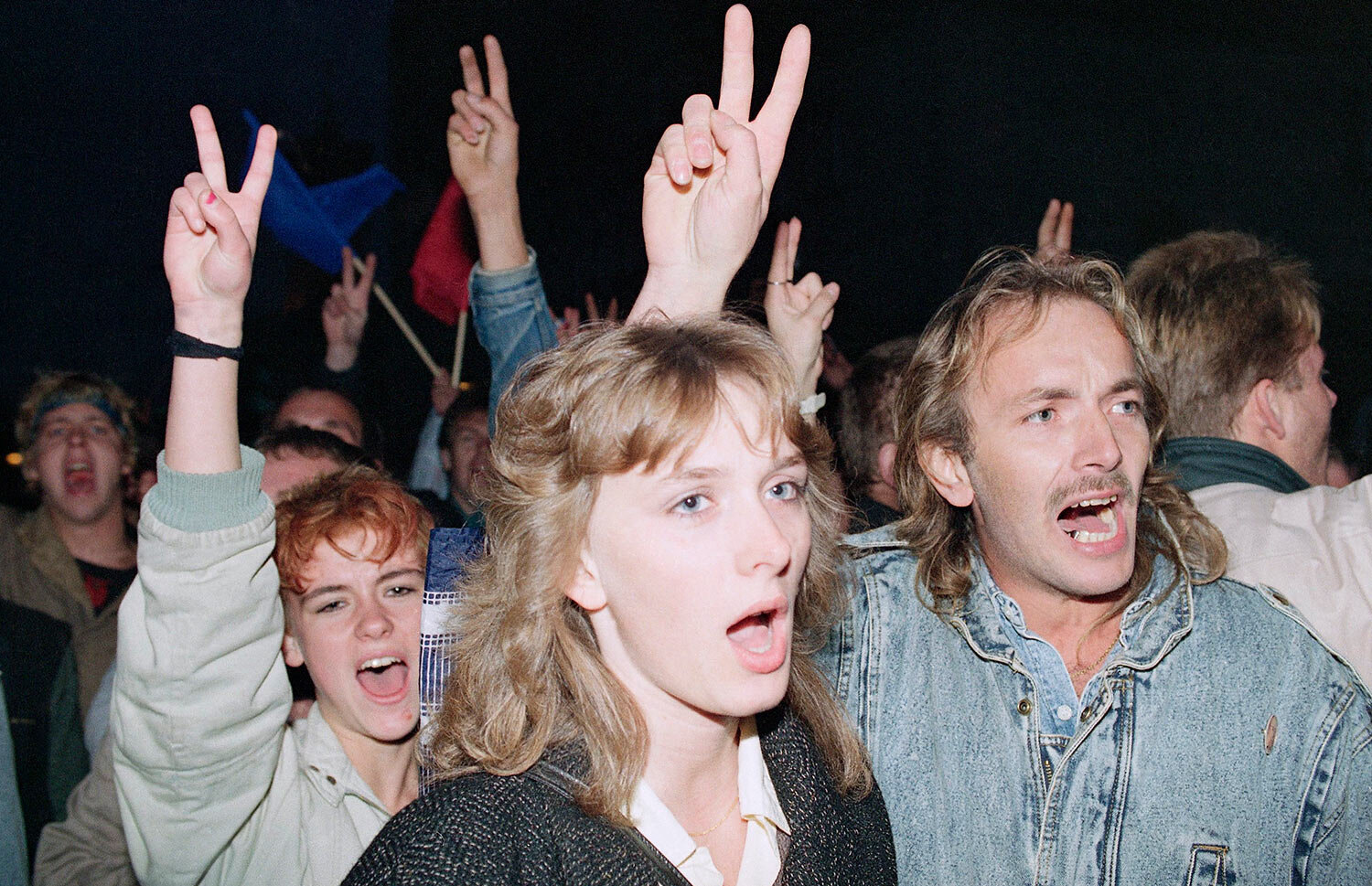 East German demonstrators flash victory signs as they demand democratic reforms in a massive protest in downtown East Berlin, Oct. 7, 1989. (AP Photo/Heribert Proepper)