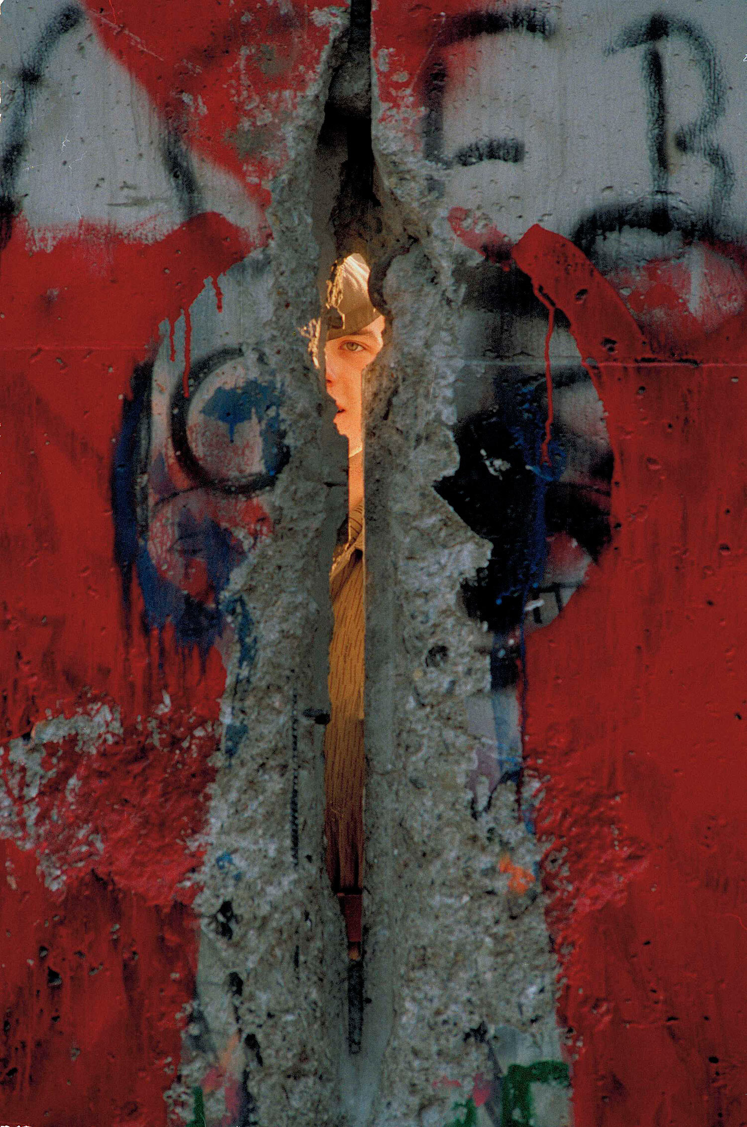 An East German border guard peers through a crack in the Berlin Wall, Nov. 17, 1989, shortly after a West Berliner painted a keyhole around the opening. (AP Photo/John Gaps III)