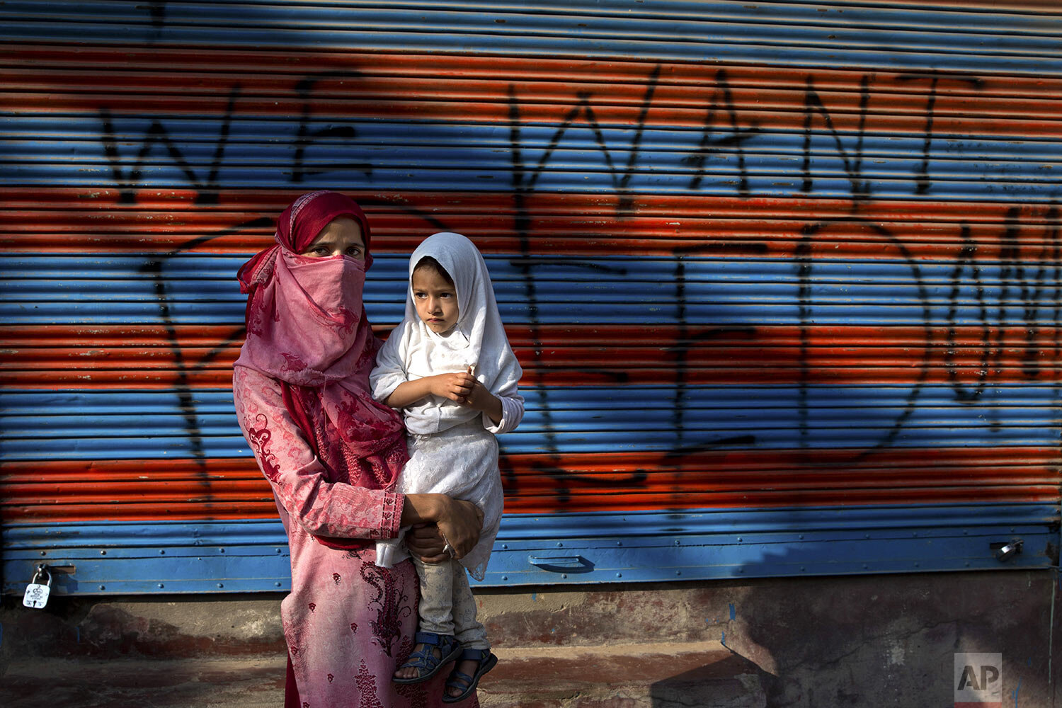 Kashmir protestor Jawahira Banoo carries her 3-year-old daughter Rutba while standing for a photograph outside a closed shop with a spray-painted graffiti message after a protest on the outskirts of Srinagar, Indian controlled Kashmir, Friday, Sept. 27, 2019. (AP Photo/ Dar Yasin)