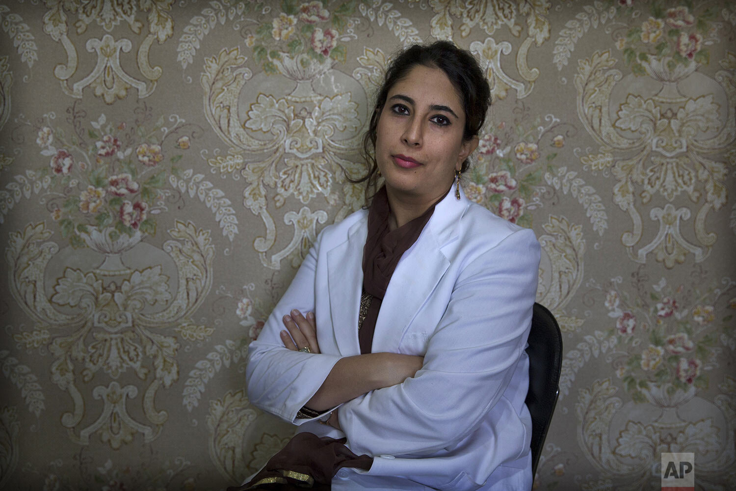 Kashmiri doctor Sabahat Rasool sits for a photograph inside her clinic in Srinagar, Indian controlled Kashmir, Friday, Sept. 27, 2019. (AP Photo/Dar Yasin)