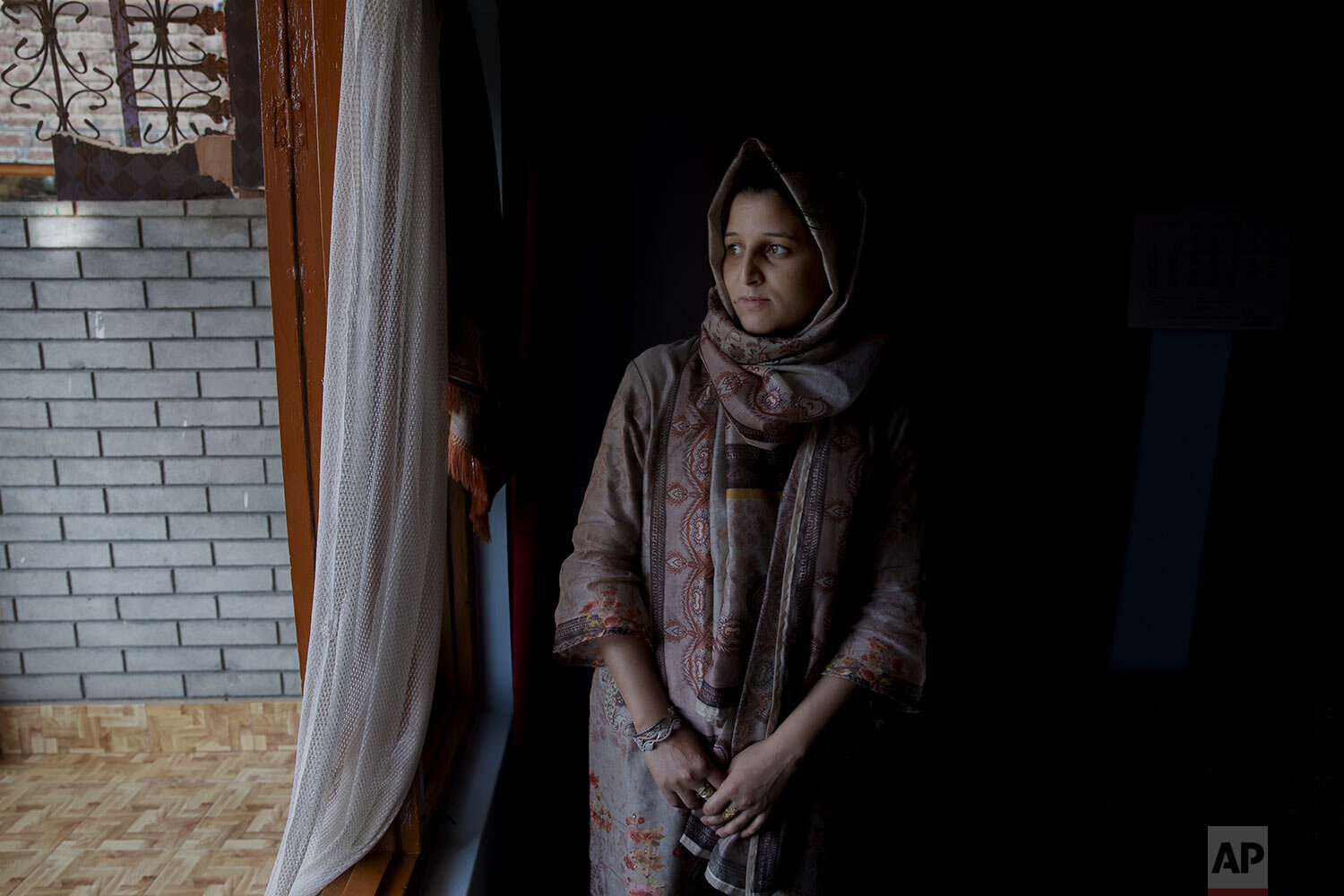 Kulsuma Rameez stands for photographs inside her home on the outskirts of Srinagar, Indian controlled Kashmir, Monday, Oct. 14, 2019. (AP Photo/ Dar Yasin)