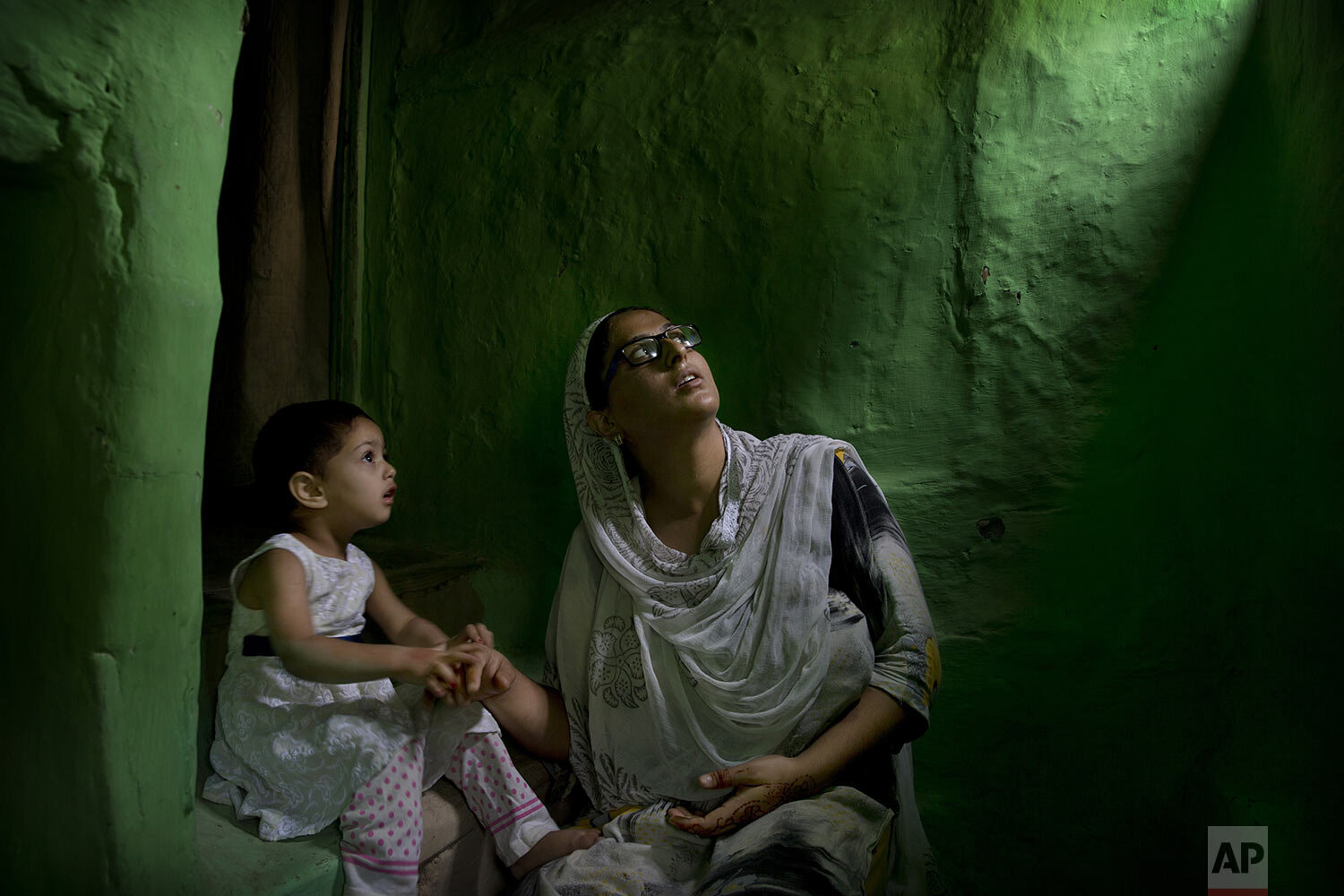Sumaira Bilal, wife of Kashmiri detainee Bilal Ahmed, talks to her two-year-old daughter as they sit for photographs on a staircase of their house in Srinagar, Indian controlled Kashmir, Friday, Sept. 27, 2019. (AP Photo/ Dar Yasin)