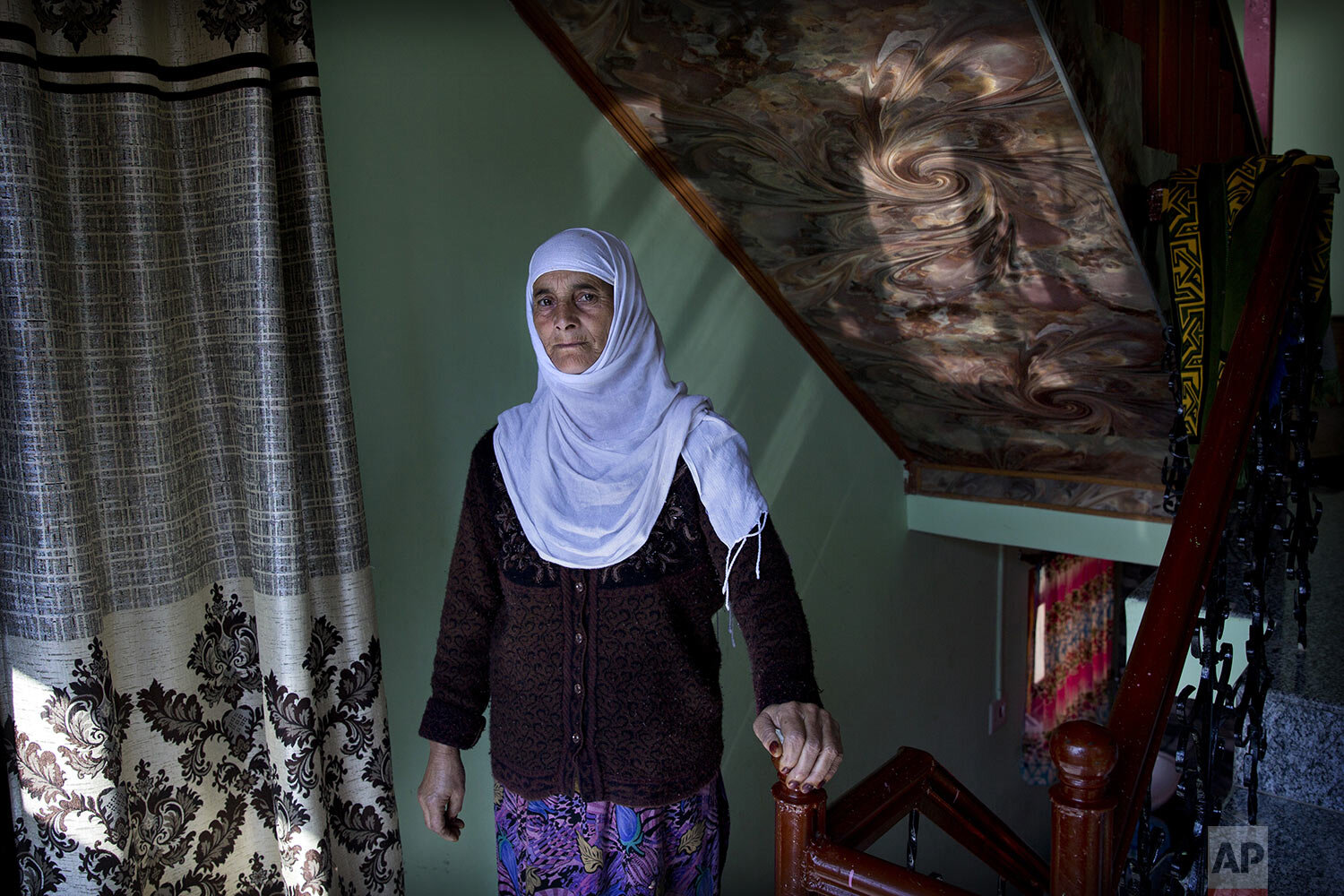 Biba Malla stands for a photograph inside her house on the outskirts of Srinagar, Indian-controlled Kashmir, Friday, Oct. 14, 2019. (AP Photo/ Dar Yasin)