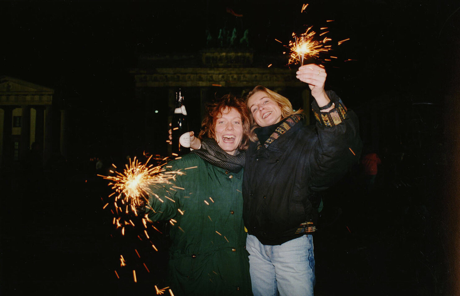Kirsten, right, and Uta, left, from West Germany hold sparklers and a bottle of champagne as they wait on the New Year at the Brandenberg Gate, Dec. 31, 1989. Thousands of of visitors from East and West Germany will meet for a joint New Year's celebration. (AP Photo/Roland Melbrauch)