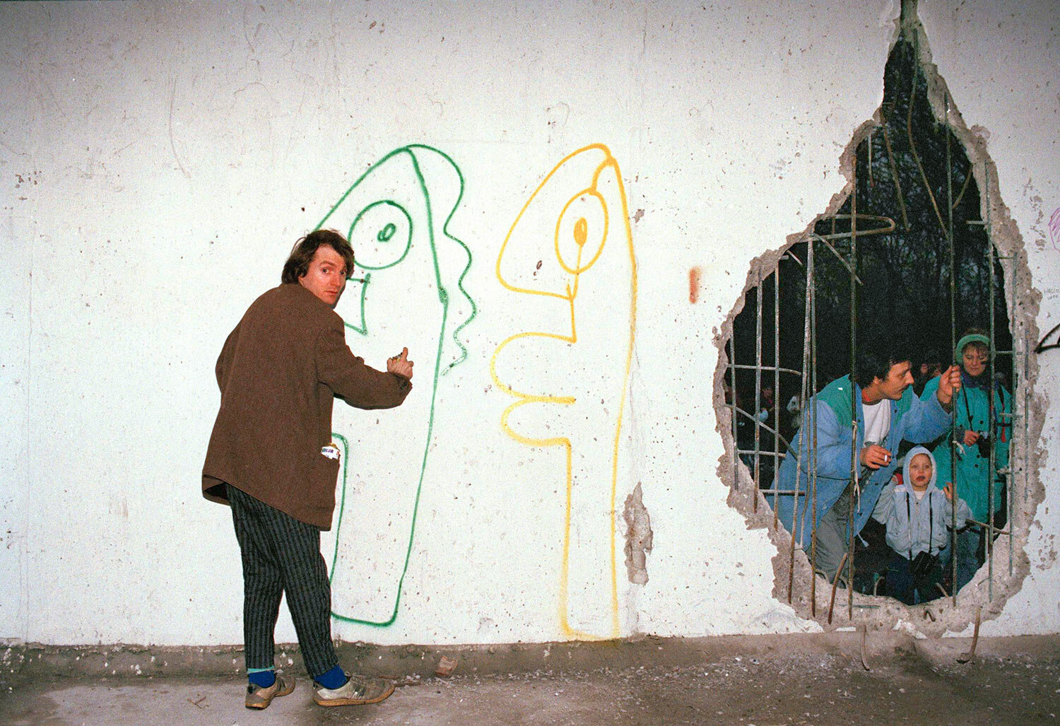 Thierry Noir of West Berlin sprays graffiti on the Berlin Wall in East Berlin near the Brandenburg Gate, Jan. 13, 1990. Before he could finish the job, East German police came and he had to escape through the hole in the wall. (AP Photo/Hans Joerg Krauss)