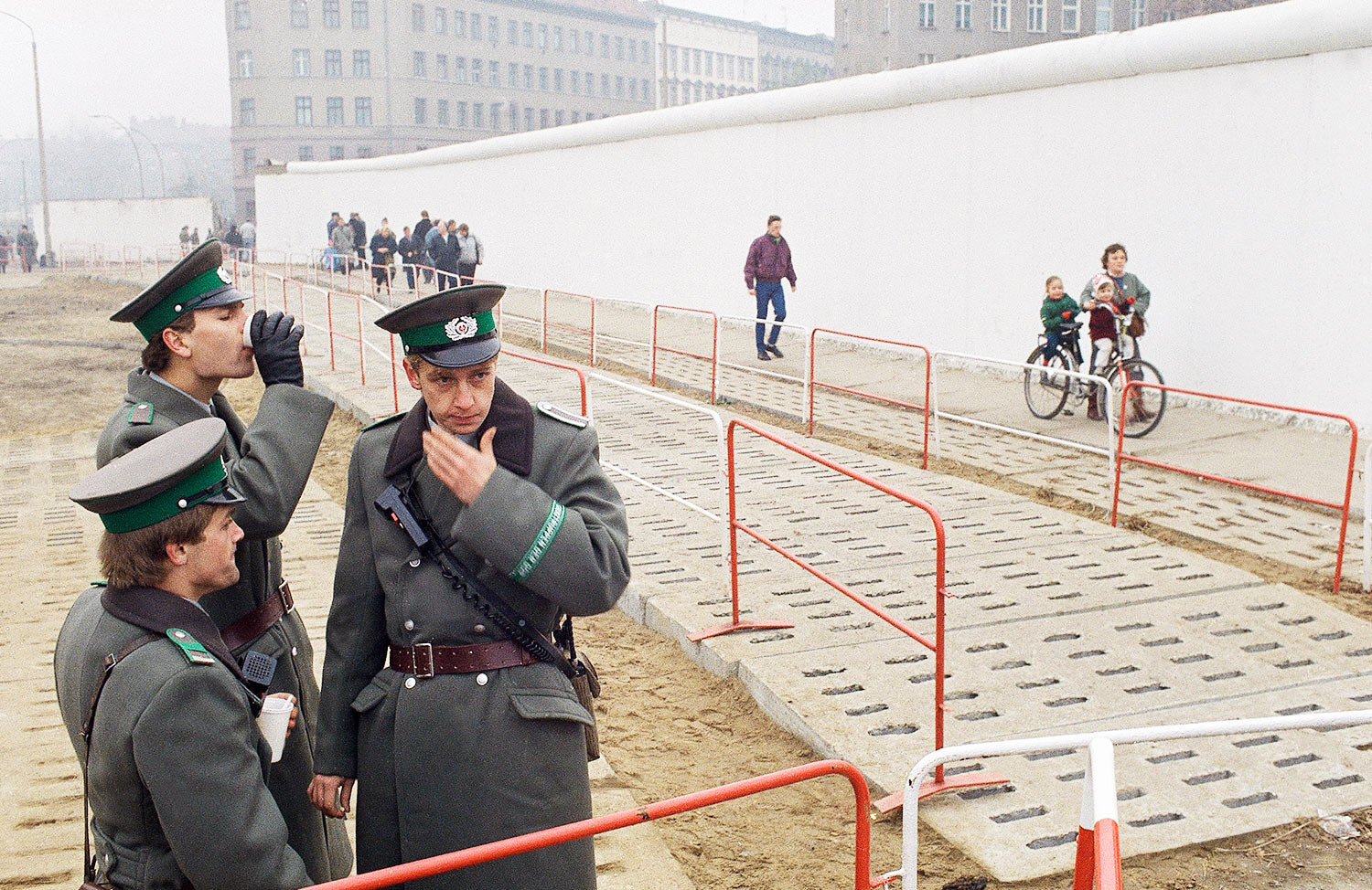 East German border guards have a coffee break atop of platform while looking down to just a few East German citizens moving into the west at Bernauer Strasse passage, in Berlin, Nov. 13, 1989. (AP Photo/Jockel Finck)