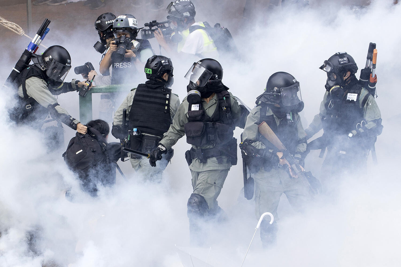 Police in riot gear move through a cloud of smoke as they detain a protester at the Hong Kong Polytechnic University in Hong Kong, Monday, Nov. 18, 2019. (AP Photo/Ng Han Guan)
