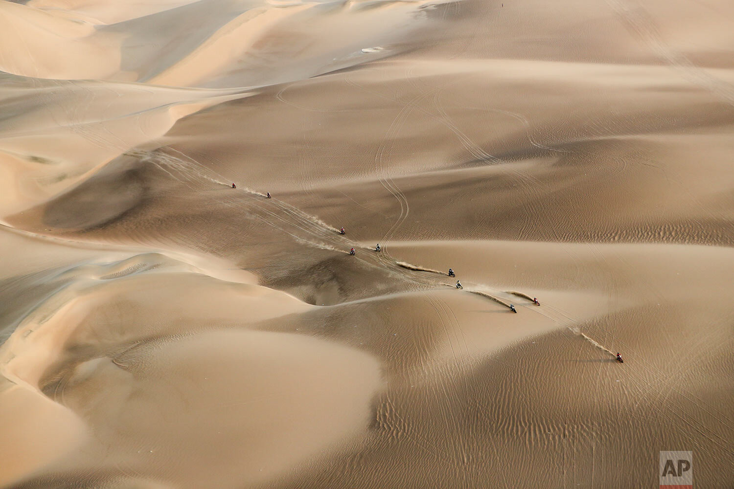 Competitors ride their motorcycles across the dunes during stage nine of the Dakar Rally in Pisco, Peru, on Jan. 16, 2019. (AP Photo/Ricardo Mazalan)