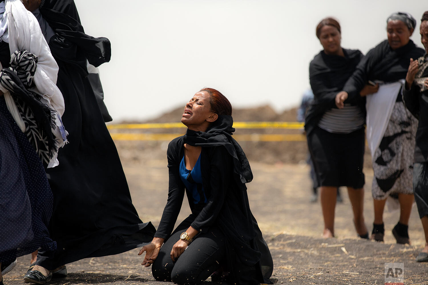 Relatives of crash victims mourn at the scene where the Ethiopian Airlines Boeing 737 Max 8 passenger jet crashed shortly after takeoff, killing all 157 on board, near Bishoftu, Ethiopia, south-east of Addis Ababa, on March 14, 2019. (AP Photo/Mulugeta Ayene)