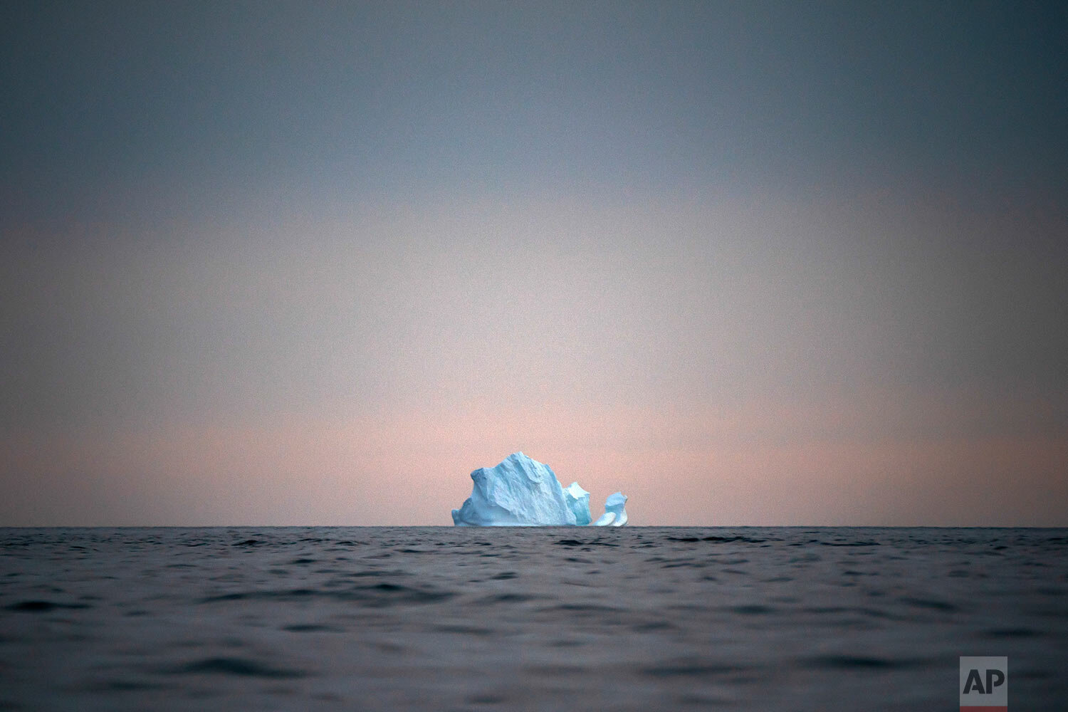 A large Iceberg floats away as the sun sets near Kulusuk, Greenland, on Aug. 15, 2019. (AP Photo/Felipe Dana)