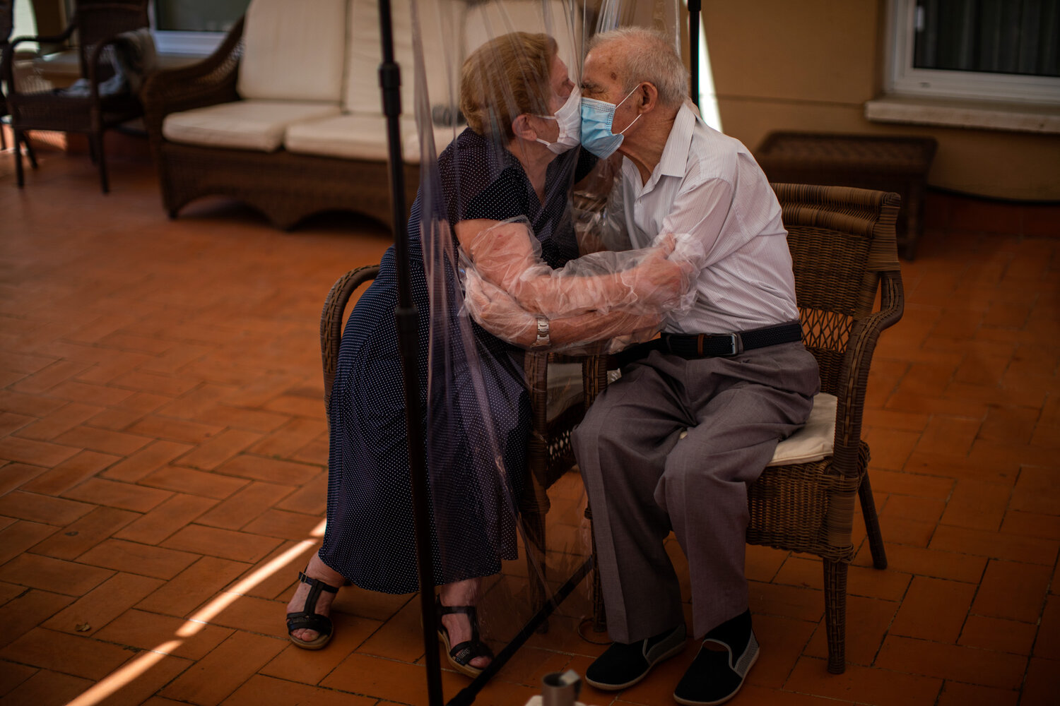 Agustina Canamero, 81, and Pascual Perez, 84, hug and kiss through a plastic film screen to avoid contracting the coronavirus at a nursing home in Barcelona, Spain, on June 22, 2020. (AP Photo/Emilio Morenatti)